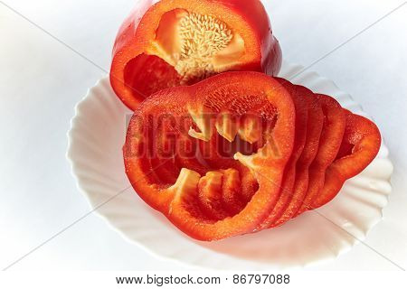 Red Bell Pepper Lies On A White Plate On A White Background, Elegant Shiny Surface Pepper, Seen Grai