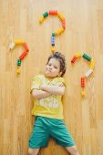 image of anger  - Little child is laying with colorful plastic blocks and given the question why - JPG