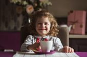 picture of girlie  - Cheerful cute girl sitting at the table  - JPG