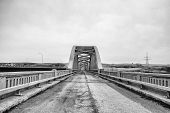 foto of old bridge  - Crumbling highway lined with guard rails leading to old abandoned concrete bridge in rural black and white landscape - JPG