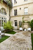 stock photo of mansion  - Plants and garden furniture in the courtyard of a French mansion - JPG