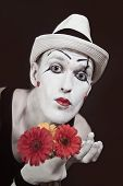 picture of mime  - Funny mime in white hat with bouquet of red gerberas on black background - JPG