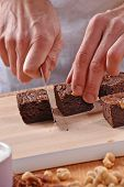 stock photo of brownie  - Pastry chef hands preparing and slicing fresh chocolate brownies on cutting board - JPG