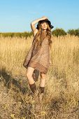 stock photo of wander  - Young lady model wandering through meadow at midday - JPG