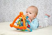 foto of teething baby  - Blue eyes baby laying on belly on soft surface and biting a colorful toy looking at the camera - JPG