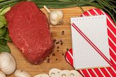 stock photo of greenery  - Raw meat and fresh greenery on a cutting board
