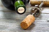 stock photo of merlot  - Close up shot of top of wine bottle cork focus on the words enjoy with rustic opener in background - JPG