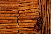 pic of cinnamon  - Cinnamon sticks and anise star on wooden background full frame - JPG