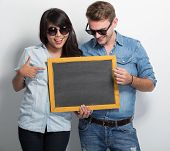 pic of multicultural  - A portrait of Happy Young Multiculture Couple posing with chalk board - JPG