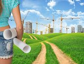stock photo of country girl  - Girl builder in jeans shorts holding paper scrolls - JPG