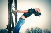 image of rebel  - young rebel woman in blue jeans and leather jacket outdoor shot on old metal construction hot sunny day - JPG