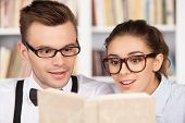 image of nerd  - Excited young nerd couple in glasses reading a book together while sitting at the library - JPG