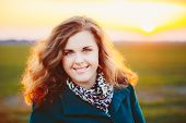 picture of plus size model  - Portrait Of Beautiful Plus Size Young Woman In Blue Coat Posing In Field Meadow At Sunset Background - JPG