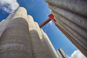 pic of silos  - Factory exterior with high concrete grain silos in Finland on a sunny spring day. This majestic old industrial building is not in use anymore. Very strong perspective from low angle view.