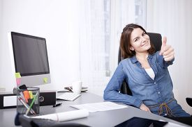 picture of gesture  - Smiling successful businesswoman giving a thumbs up gesture of success and approval as she sits at her desk in the office - JPG