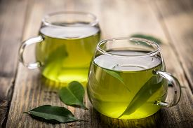 stock photo of hot water  - Fresh green tea with tea leaves in the water