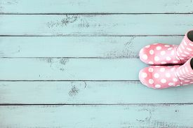 pic of rainy season  - Pink polka dot rain boots on mint blue shabby chic wooden background - JPG