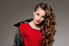 image of jacket  - Beautiful young woman model brunette with long curled hair with red lips in leather jacket - JPG