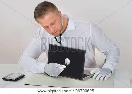 Technician Examining Laptop With Stethoscope