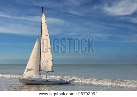 little white sailboat grounded on a beach