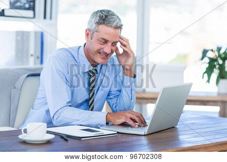 Happy businessman using laptop computer in office