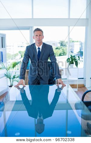 Serious businessman looking at camera in office