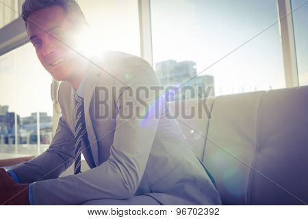 Happy business man sitting on sofa and looking at camera in living room