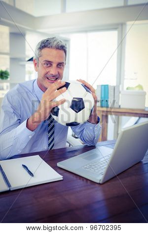 Happy businessman looking at camera and holding foot ball in office