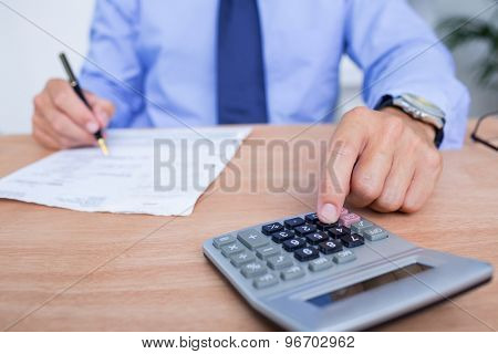 Businessman using the calculator while writing in the office