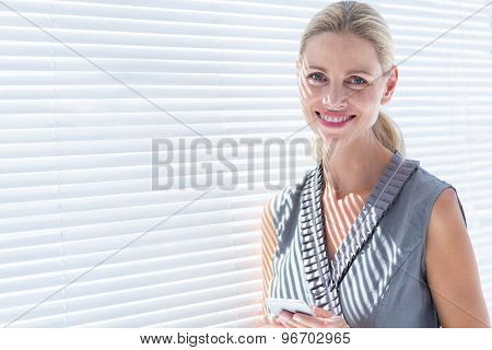 Smiling businesswoman looking at the camera while holding her phone