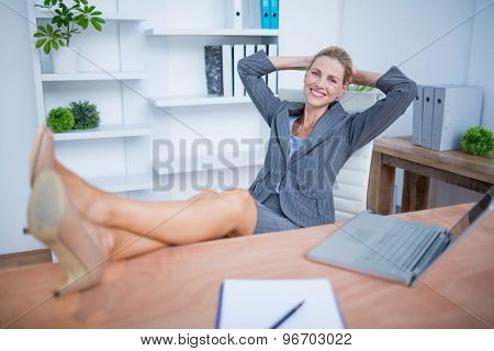Portrait of a smiling blonde businesswoman relaxing herself
