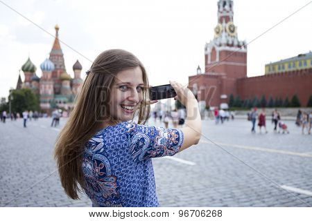 Happy young brunette woman photographed attractions in Moscow