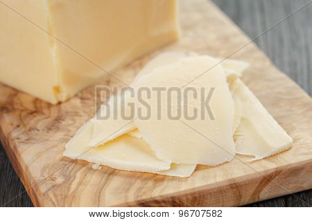 parmesan cheese sliced on olive board