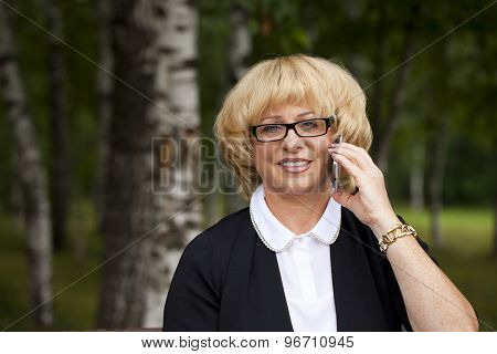 Mature beautiful blonde woman is calling on a cell phone, outdoors in summer park