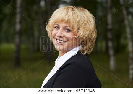 Close up portrait of serene mature woman in the summer park