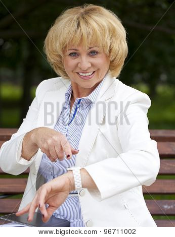 Mature business woman in a white jacket shows on his watch in the summer park