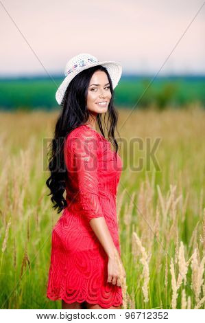 beautiful brunette woman with a red dress in a field at sunset