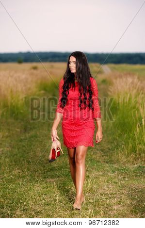 beautiful brunette woman with shoes in hand on a field at sunset