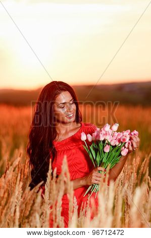 beautiful brunette woman in red dress with tulips in hands on a field at sunset