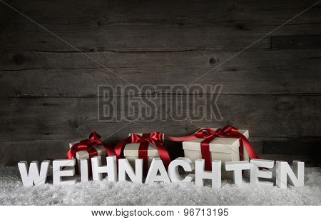 Wooden background with presents and the text christmas in german letters.