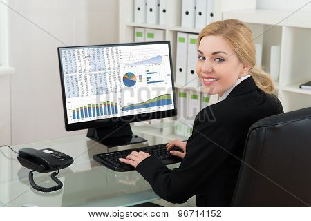 Businesswoman Smiling While Working On Computer