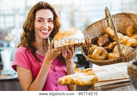 Pretty brunette showing loaf of bread at the bakery