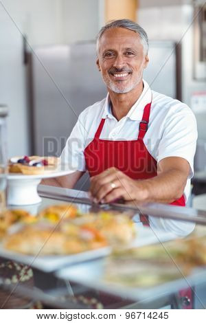 Barista smiling at camera behind counter in the bakery