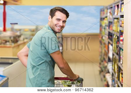 Portrait of smiling man pushing his trolley in aisle at supermarket