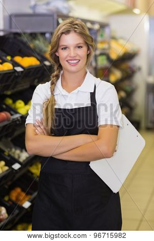Portrait of a smiling staff woman having a clipboard on her hands at supermarket