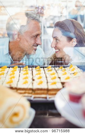 Cute couple looking at each other in the bakery store