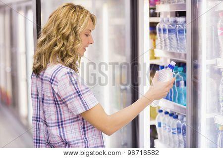Smiling blonde woman taking a water bottle in supermarket