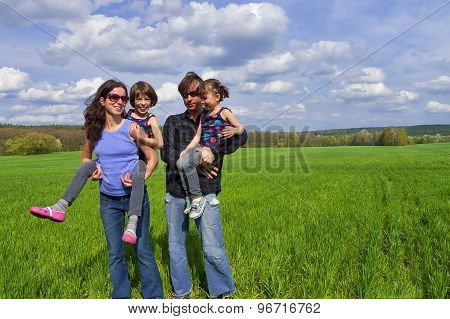 Happy family outdoors having fun. Active parents giving their kids piggyback ride