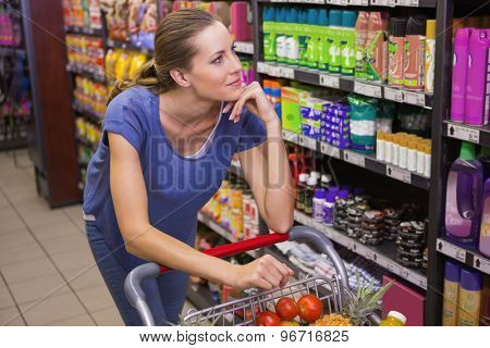 Thoughtful pretty brunette pushing trolley at supermarket