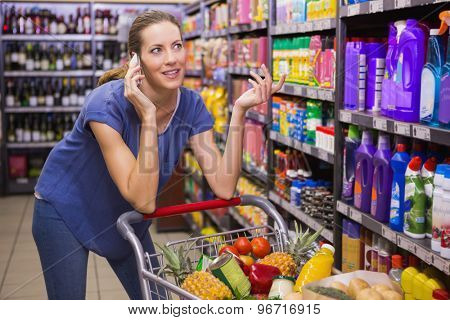 Pretty woman having a phone call and pushing trolley at supermarket